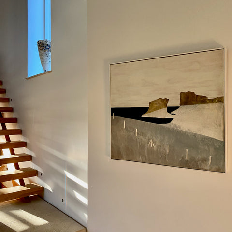 Abstract painting of field and fence hanging on a wall beside some open stairs with sunlight shining through the stair treads.