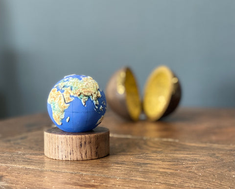miniature blue and yellow globe on a wooden stand with its round box in the background it was made by loraine Rutt of the little globe company