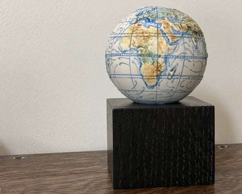 miniature globe on a dark wooden stand it was made by loraine Rutt of the Little Globe company