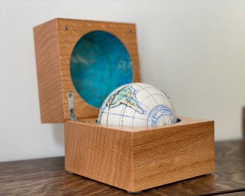 a small globe in a wooden box with the inside of the lid painted blue it was made by Loraine Rutt of the Little Globe company
