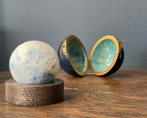 minature ceramic blue moon on a wooden stand with a round case behind it is made by Loraine Rutt of the Little Globe company
