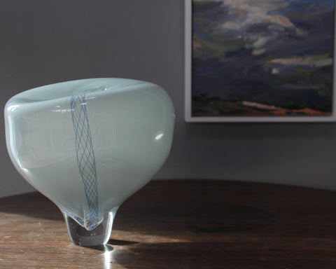 pale blue round glass vessel next to corner of landscape painting