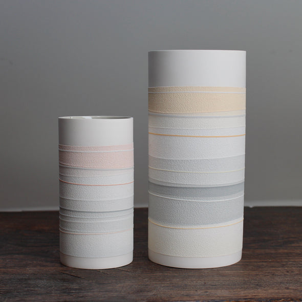 two white ceramic cylinder vases with pale orange and grey stripes.