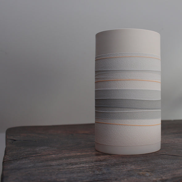 a white ceramic cylinder vase with pale orange and grey stripes.