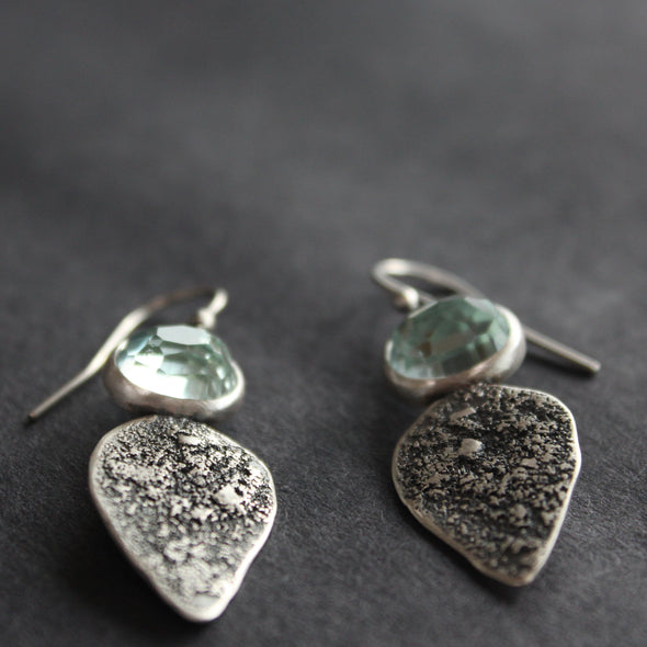 Textured silver with aquamarine stone drop earrings on a dark grey background