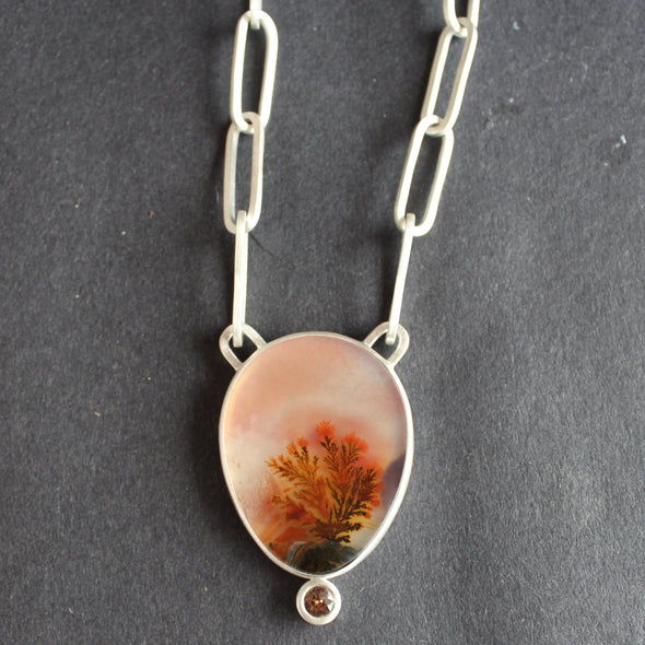 Rose coloured agate stone in a teardrop cut set in silver with a large linked chain a small pink stone set at the very bottom