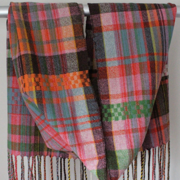 Handwoven scarf with orange, pink and green hanging over a display rail