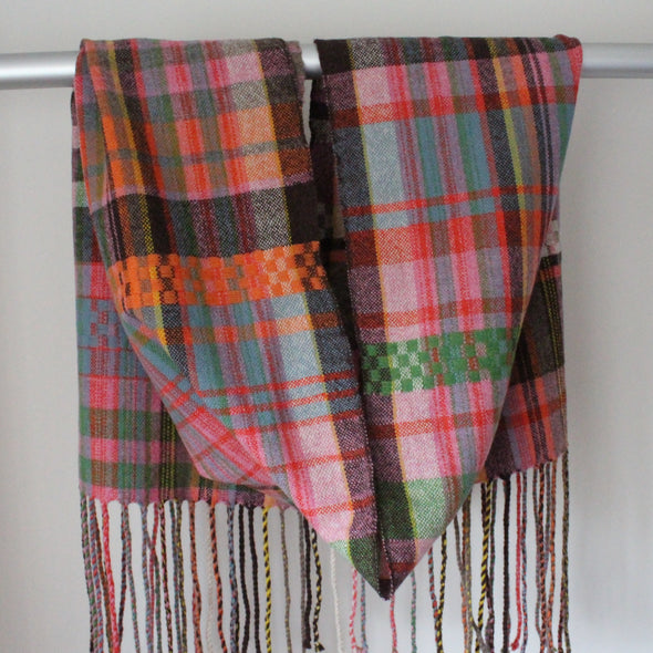 A Handwoven scarf with orange, pink and green hanging over a display rail