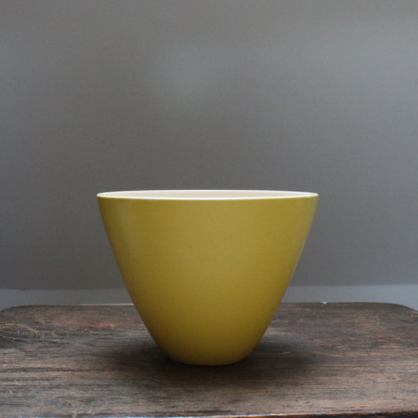 A yellow bowl Lucy Burley on a wooden table