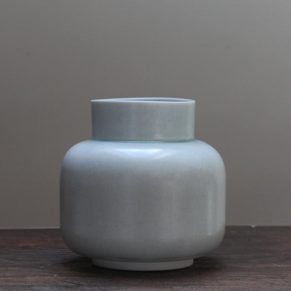 Pale Green ceramic vase by ceramicist Laura Plant on a wooden table