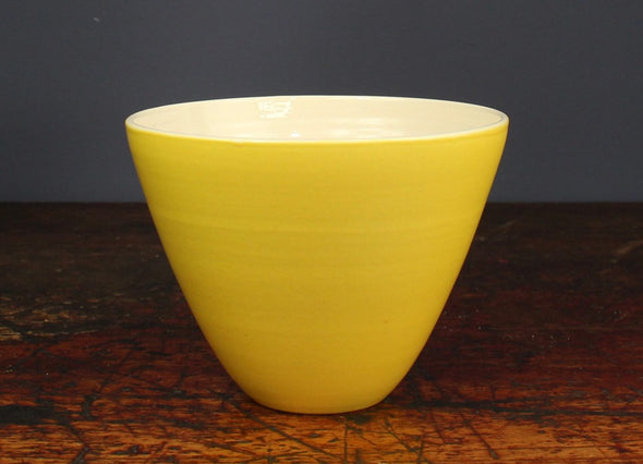 Tall yellow bowl Lucy Burley on a wooden table