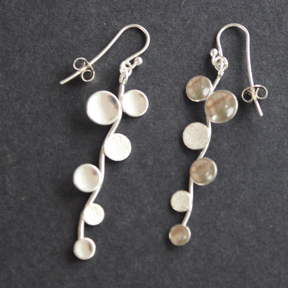 Long sliver earrings of small circles attached to central curved line made by Beverly Bartlett