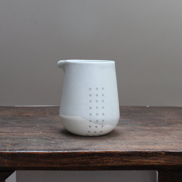 Pale green jug with partial grey pattern of spots on a wooden table