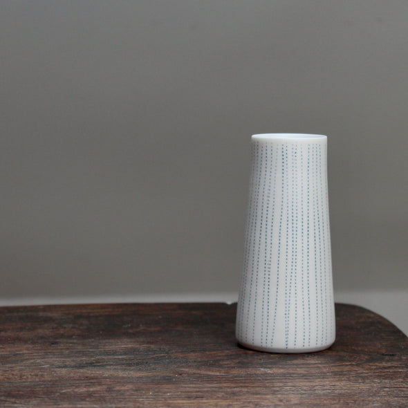 narrow ceramic white stem vase with vertical blue lines on a wooden table