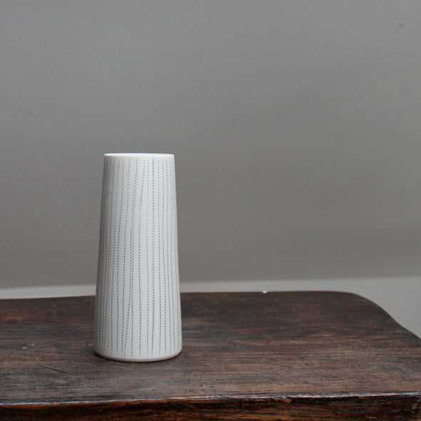 A narrow ceramic white stem vase with vertical blue lines on a wooden table .