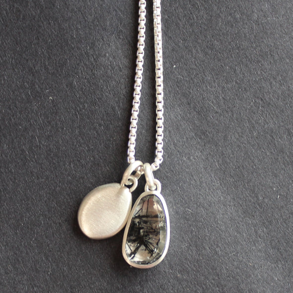 Double silver pendant irregular shaped silver disc and quartz set in silver on a silver chain.