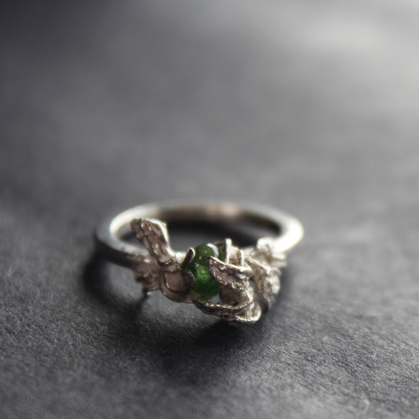Silver ring with textured claws holding a green stone