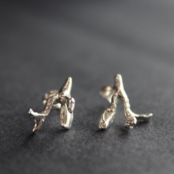 A mis-matched pair of textured silver stud earrings cast from seaweed