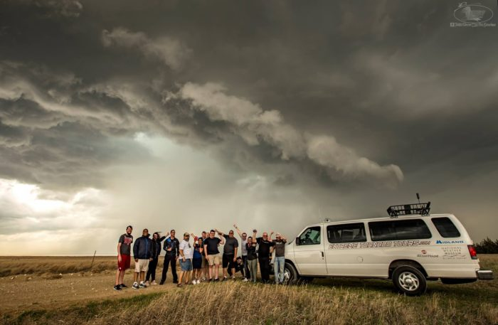 Group of people on storm chasing tour standing in wheat field next to white van with tornado developing in the background