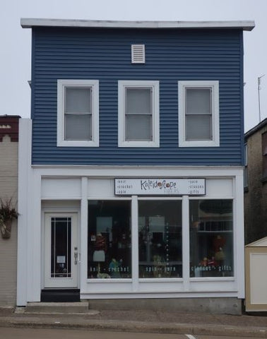 "Picture of physical storefront for Kaleidoscope Fibers, showing a blue building with white trim and a sign that says ""Kaleidoscope Fibers""."