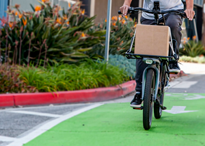 Rider biking on a CERO One with a Platform carrying a cardboard box.