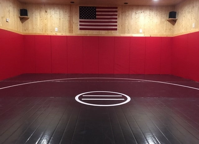 Home wrestling room black mat with red wall pads