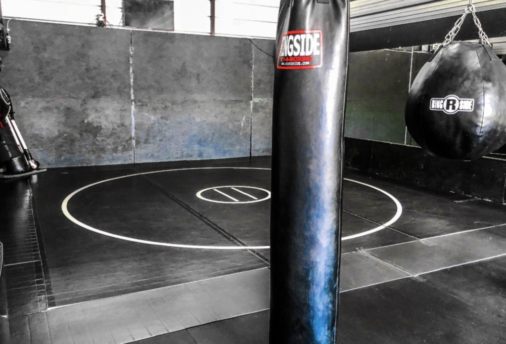 Black training room with AK wrestling mat