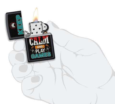 Zippo aansteker zwart met inscriptie Keep Calm and Play Games geopend met vlam in gestileerde hand