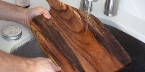 Running a wooden serving board under water.