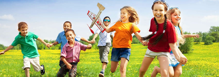 Kids play outside with balsa airplane