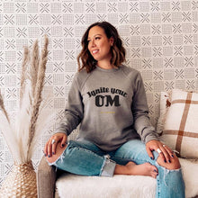 Load image into Gallery viewer, Radiate good energy in our Ignite Your OM Classic Crew Sweatshirt, featuring a rib crewneck, raglan sleeves, and 'Ignite Your OM' front graphic printed with eco-friendly inks. Relaxed, slightly oversized fit. Made with 50% cotton and 50% polyester for ultimate coziness.