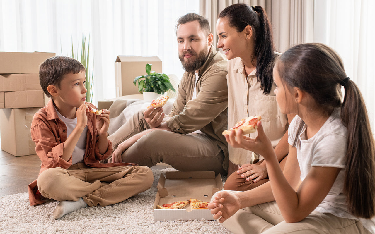 Friendly family eating pizza in new house
