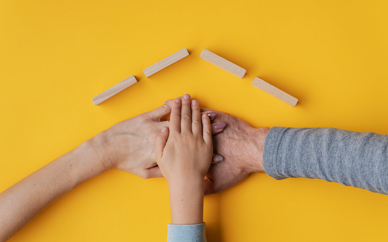 Family stacking their hand on yellow background with roof made of wooden blocks above their hands