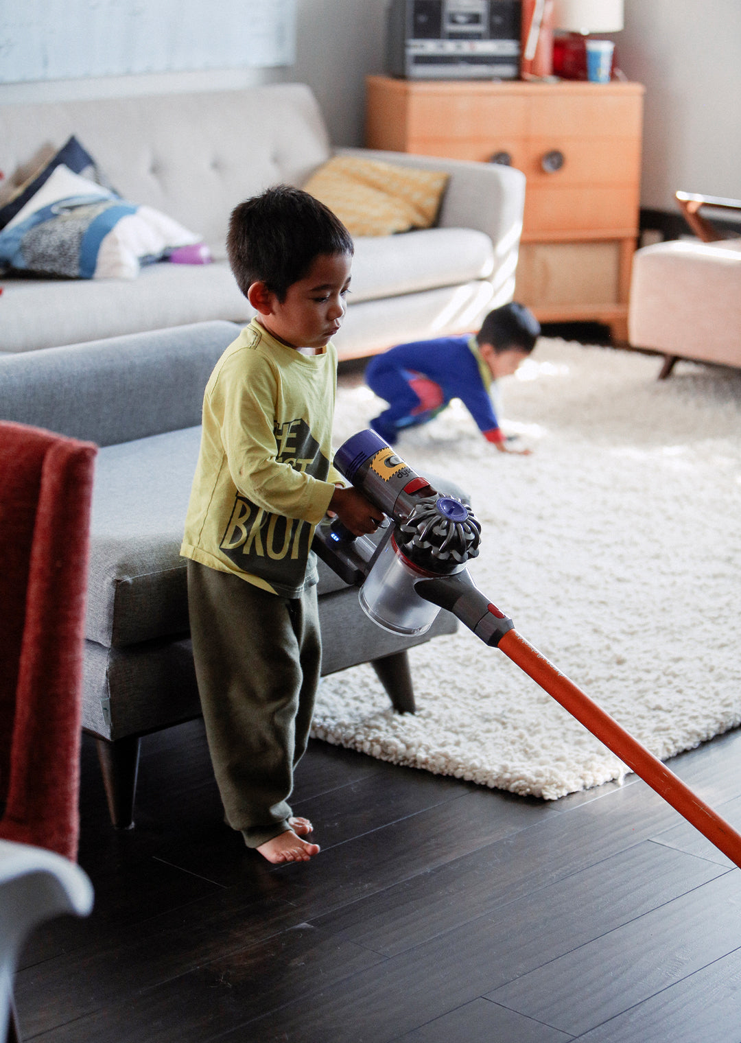 Young diverse little boy vacuuming the living room of his house doing chores