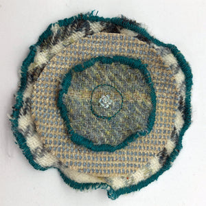 Flower shaped brooch handmade by Rose-May using a tweed and fabric in the shape of a flower. Glass beads are hand sewn into the centre.