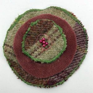 Rose-May tweed brooch handmade using a patterned tweed and plain pink fabric. Finished with a bead centre detail. Pin handsewn onto back.