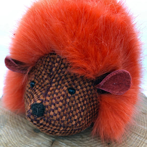 Striking orange hedgehog plushie. Made with luxuriously soft faux fur with a woven fabric face and body finished with leather ears and a hand embroidered nose. Wonderfully bright and quirky looking.  Complete with a gift box.