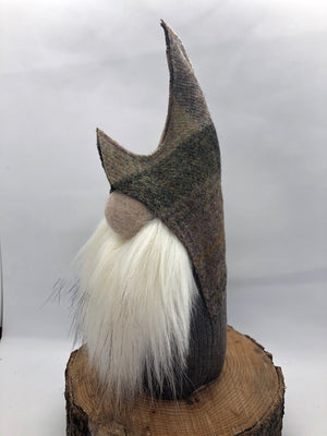 Delightful gnome made using tweed for the hat and a light purple coloured fabric body. The beard is a luxurious full and soft faux fur finished with a large felted wool nose.