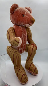 A very individual looking bear made in Britain by bears artists Rose-May. Made from silk this bear has striped patterns on the arms and legs and plain coloured body and head. Fully jointed with glass eyes a real individual looking bear. Measures 31cm in length.