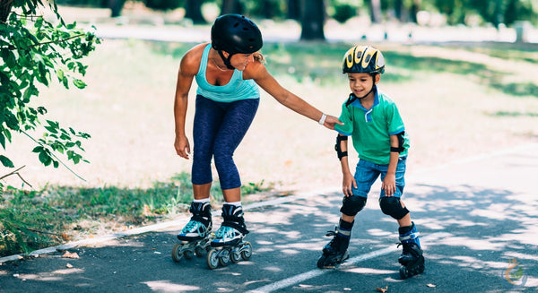Mom and child roller skating outside in the summer with helmets and padding on