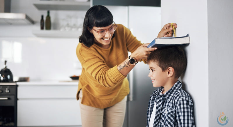 Mom with dark hair, bangs, and glasses, measures her sons height against the wall with a book and a pencil