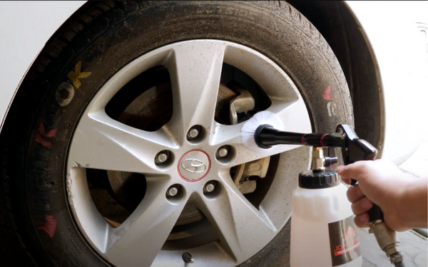 using a car cleaning gun to detail tires and wheels