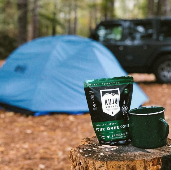 Travel pack of Basecamp Blend Pour Over Coffee at a campsite with a mug and a tent.