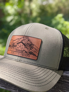 "Trucker hat with black mesh on back, olive green colored front and leather patch depicting the Mission and Madonna Mountain. The patch reads ""San Luis Obispo."""