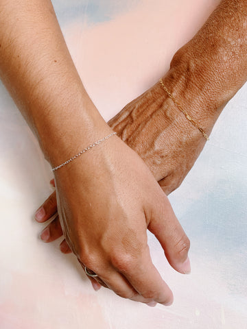 two hands with bracelets
