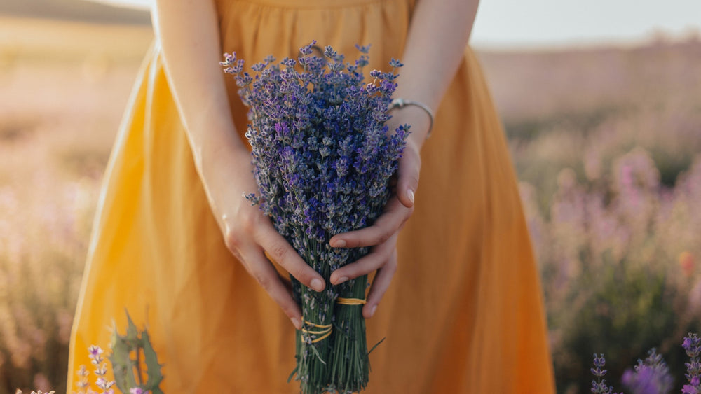 JWLRY Banner Girl with bracelet in yellow dress holding lavender.