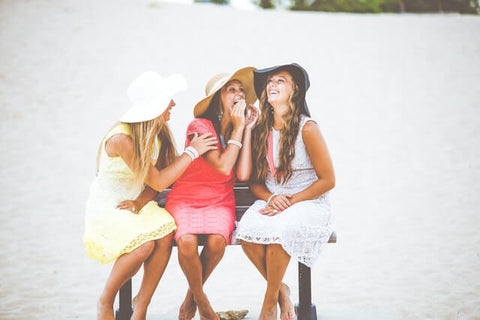 Top 5 reasons for smiling more + Happines + JWLRY + Three happy ladies with hats on a bench whispering and laughing.