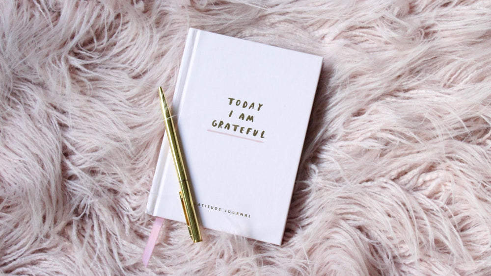 "JWLRY Banner - ""Today I An Grateful"" book with golden pen lying on a fluffy purple blanket."