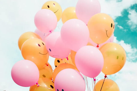 Top 5 reasons for smiling more + Smile + JWLRY + Pink and orange helium balloons with smiley faces hanging in front of a blue sky with white clouds.