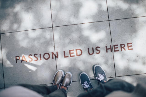 """The need for more positivity + Passion + JWLRY + """"Passion led us here"""" printed on concrete tiles on the floor and two sets of feet with nice trousers and shoes on."""